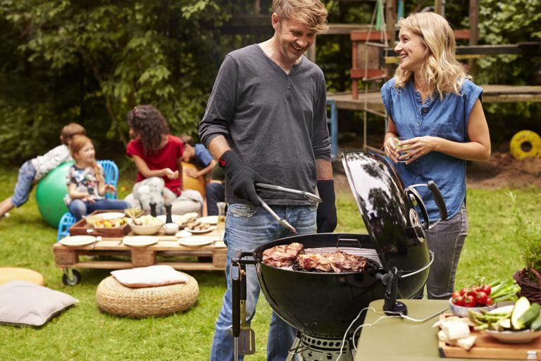 Family cooking steak on a Weber barbecue grill
